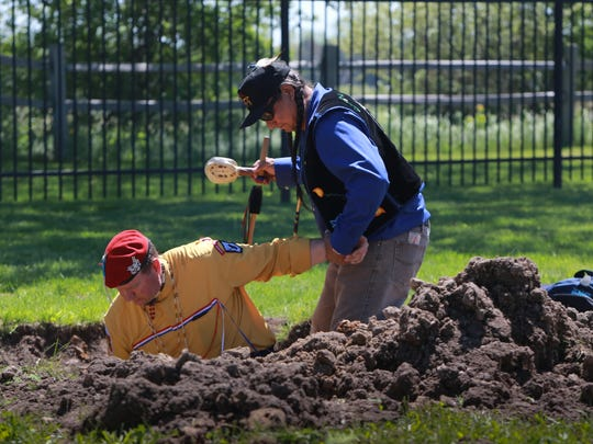 Brian Corbiere, 52, of Mount Pleasant helps Saginaw Chippewa tribe member Tony Perry of Elwell out of a  grave.