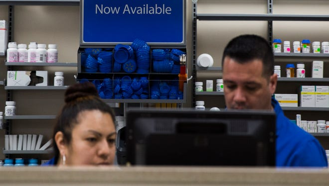 Walmart pharmacy cashier Nadia Ramirez, left, and pharmacy technician Victor Mirabal, right, work on a computer at the Walmart pharmacy at U.S. 41 and Immokalee Road in North Naples on Thursday, Feb. 8, 2018.