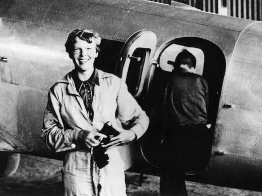 In this 1937 photo, Amelia Earhart prepares to board her modified Lockheed airplane as navigator Fred Noonan climbs inside during a stop at Parnamerim Airfield, Brazil.