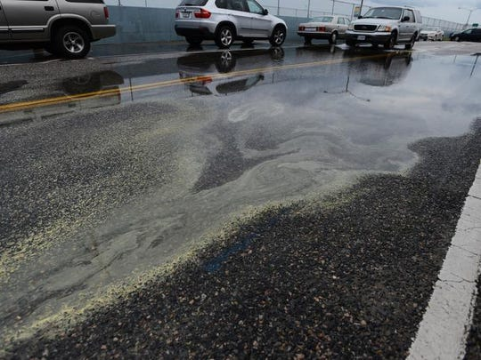 Pollen collects in a rain puddle before the Chesapeake Bay Bridge-Tunnel after a heavy rain.