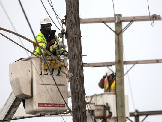 Lineman work on swapping out old streetlights as crews