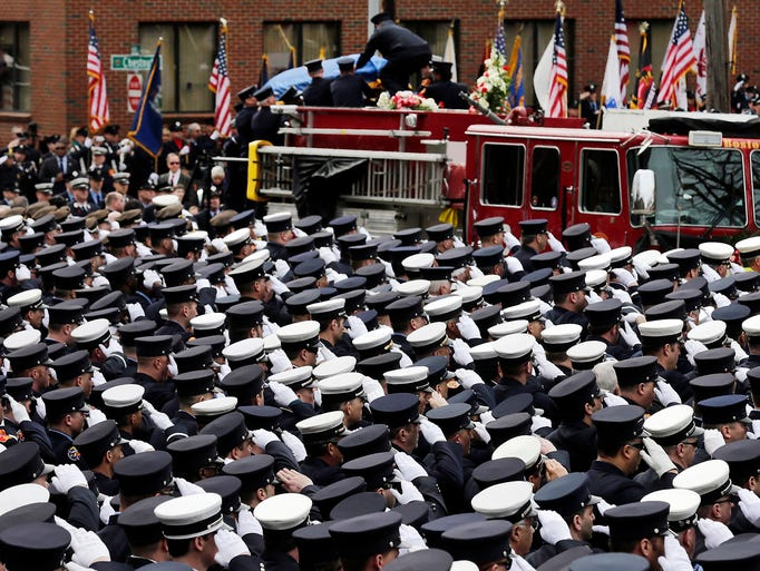 Firefighters salute as the casket of Boston fire department Lt. Edward Walsh is lowered from Engine 33 outside St. Patrick's Church on April 2 in Watertown, Mass. Walsh and fellow firefighter Michael Kennedy died on March 26 when they were trapped while battling a nine-alarm apartment fire in Boston.