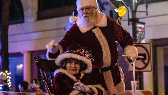 Santa and Mrs. Claus wave to spectators gathered along East Main Street for the Deck the Halls holiday parade in downtown Richmond on Friday, Dec. 1, 2017.
