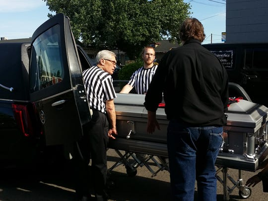 Travis Lane's casket is loaded into a hearse. Lane was a big fan of the Portland Trail Blazers, so funeral home employees wore referee shirts.