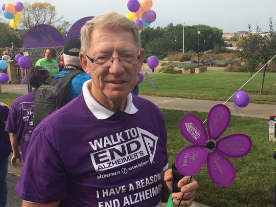 Mike Hanna, a participant in the Walk to End Alzheimer's, held a flower in memory of his father, a caregiver to his mother who lives with Alzheimer's, at the Des Moines Capitol building on Saturday, Sept. 20, 2014.