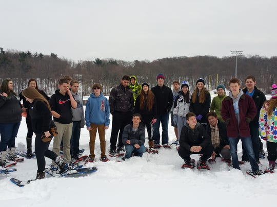 Members of a Millbrook High School gym class pose for a photo during a snowshoeing unit.