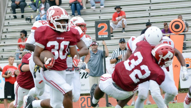 Pineville's Quadrell Jimmerson (30) runs against Tioga Saturday. Jimmerson scored the game-winning touchdown in Pineville's 26-21 home victory.