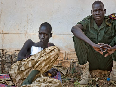 A wounded soldier sits with a colleague in an outside courtyard at the Juba Military Hospital in Juba, South Sudan on Dec. 28, 2013. A spokesman for South Sudan's military says fighting continues in the oil-producing Unity state despite ongoing effor