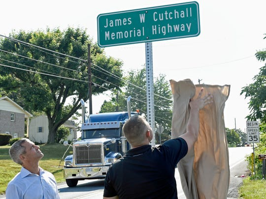 "Rep. Robb Kauffman, left, watches as Jacob Cutchall unviels a new road sign. Main Street in Fayetteville has been renamed after firefighter James ""Jim"" Cutchall who was killed by a sniper in July 1977 while responding to a fire alarm. Jacob is the nephew of Jim Cutchall."