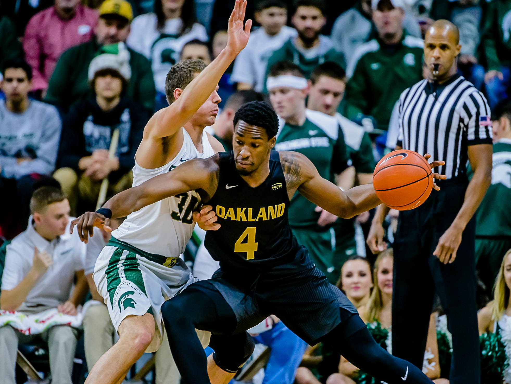 Oakland's Jalen Hayes, a Lansing Sexton alum, drives to the basket before scoring over MSU's Matt Van Dyk early on during their game Wednesday night at Breslin Center.