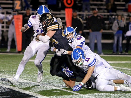 Henrietta's Zack West is brought down by Childress' Isaiah Darter (15), Aric Furr (40) and Kaden Hunter (11) during a rushing attempt on Sept. 29 in Henrietta.