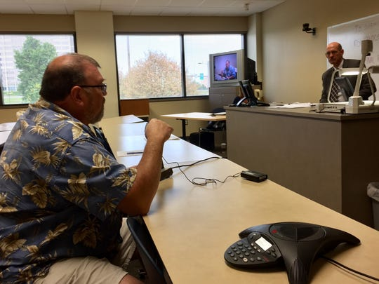Consumer David Fairchild of Story City, left, tells Insurance Commissioner Doug Ommen about the burden of buying increasingly expensive individual health insurance. Fairchild spoke at a hearing Saturday on Medica's proposed 57% premium increase.
