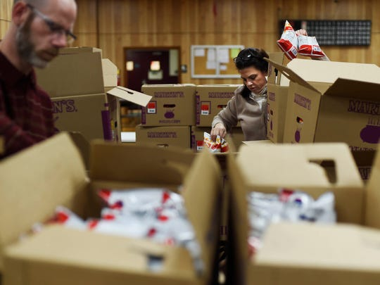 Ryan Krebs of Springettsbury Township, left, and Cheri Booth of Red Lion pack boxes with chips for Valentine's Day care packages for troops serving overseas at Alert Fire Hall in Emigsville. Rutters and SOAR, Support Our American Recruits, teamed up for the 11th year to send candy, chips, and magazines.