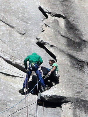 Kevin Jorgeson of California, wearing green, and 36-year-old Tommy Caldwell, wearing blue, near the summit of El Capitan Wednesday, Jan. 14, 2015, as seen from the valley floor in Yosemite National Park, Calif. The two climbers became the first in the world to use only their hands and feet to scale a sheer granite face in California's Yosemite National Park.
