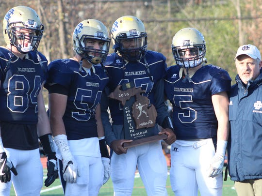 Country Day players Cole Bearden (84), Adam Fakih (54), Jalen Graham (17) and Chris Bergin (5) accept the regional championship trophy from Athletic Director Dan Luft.