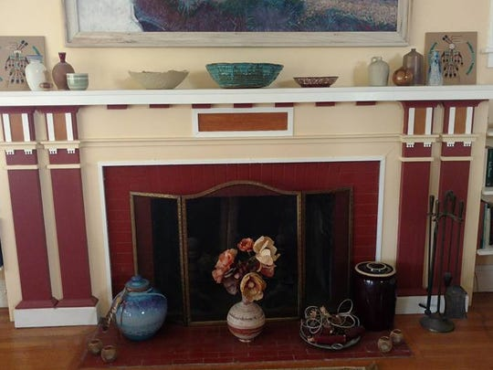 The fireplace in the living area of Mary D. Wells' home features woodwork typical of the Craftsman era.