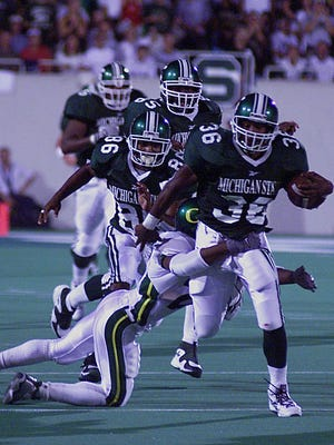 MSU tailback Lloyd Clemmons drags Oregon's Tamoni Joiner on a 35-yard gain in the Spartans' 1999 win over the Ducks at Spartan Stadium, the last time Oregon visited East Lansing.