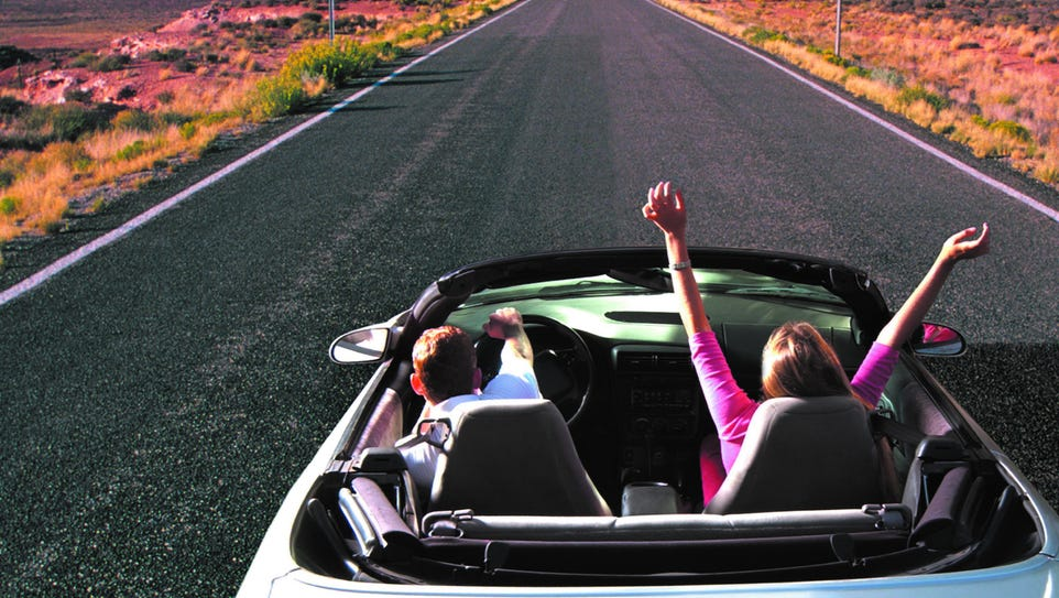 Photo, couple riding in a convertible on a desert highway,