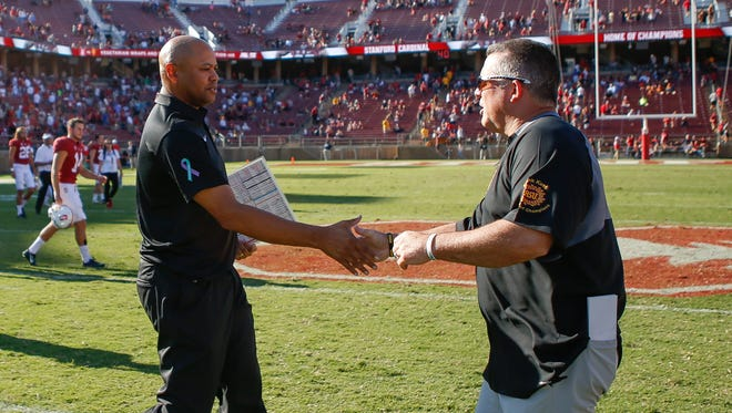 Stanford Cardinal head coach David Shaw (left) shakes hands with Arizona State Sun Devils head coach Todd Graham after winning the game at Stanford Stadium.