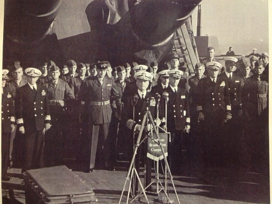 U.S. Marine Corps 1st Lt.  Bill Weed (in front, hands behind back) stands just to the left of Adm.  William Halsey (speaking at microphone) aboard the USS South Dakota on Nov. 22, 1945.