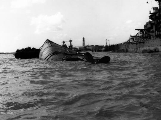 The capsized hull of USS Oklahoma (BB-37), with a barge alongside to support rescue efforts, probably on 8 December 1941. USS Maryland (BB-46) is at right, and USS California (BB-44) is in the center distance. Official U.S. Navy Photograph, now in the collections of the National Archives.