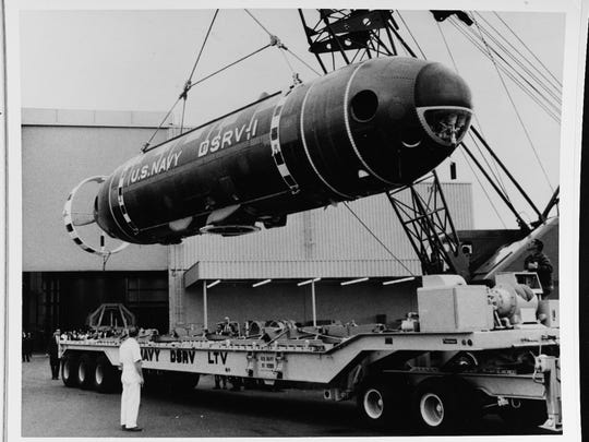 "Sunnyvale, California. The Navy's deep submergence rescue vehicle (DSRV) is loaded onto its flatbed trailer for transport to the airfield. The prototype submersible will be airlifted to San Diego for launching on 24 January 1970. It was built by Lockheed Missiles and space Co. and is destined to rescue up to 24 men at a time from disabled subMarines. The small submergible is capable of ""mating"" with the escape hatch of a downed subMarine and transferring crewmen and is expected to operate at depths down to 5,000 feet. Dated January 1970."