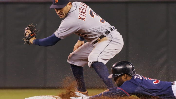 Minnesota Twins' Danny Santana, right, doubles off Detroit Tigers pitcher Rick Porcello as he beat the tag by Detroit Tigers second baseman Ian Kinsler in the fifth inning of a baseball game, Tuesday, Sept. 16, 2014, in Minneapolis.
