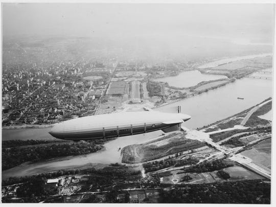 The USS Akron flies over Arlington, Virginia, with the Potomac River and Washington, D.C., in the background, circa 1931-1932.