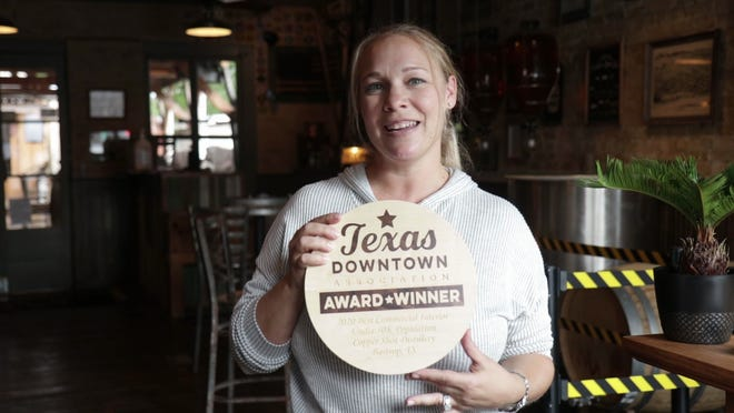 Cheri Todee, a founder and owner of Copper Shot Distillery in Bastrop, poses with the Texas Downtown Association 2020 award for Best Commercial Interior in a city with a population under 50,000.
