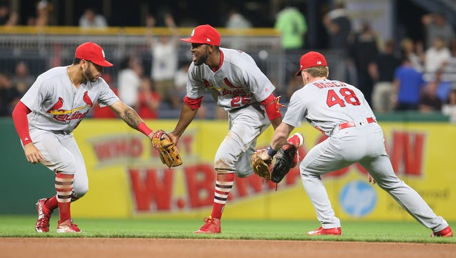 Cardinals outfielders, from left to right, Tommy Pham, Dexter Fowler and Harrison Bader celebrate after defeating the Pirates at PNC Park in Pittsburgh.