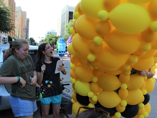 Katherine Strader, an eighth-grader from Tyler, reacts to an up close and personal visit by a yellow crayon. Her cousin, Olivia Law, of Abilene, seems to be more apprehensive during Thursday's Storybook Parade.