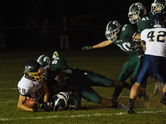 Highland's Andrew Ligotino, bottom, gets tackled by