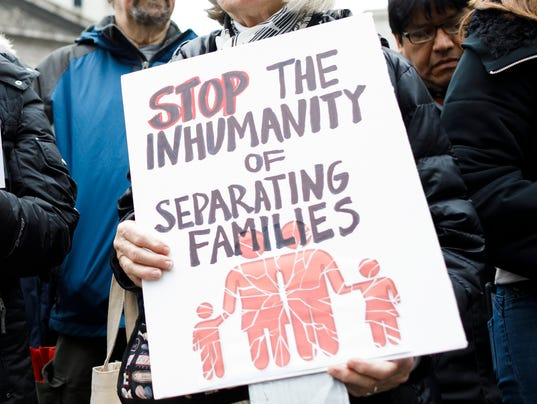 "Image shows protester holding a sign reading ""stop the inhumanity of separating families"""