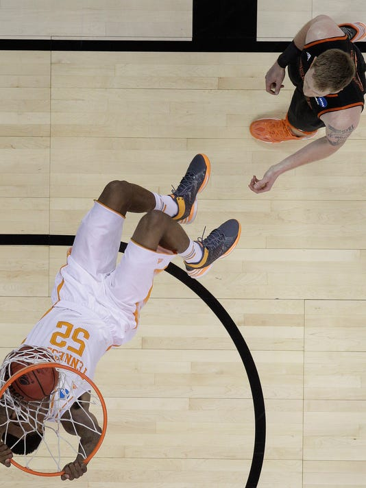 Tennessee guard Jordan McRae (52) dunks against Mercer forward Jakob Gollon (20) during the first half of an NCAA college basketball third-round tournament game, Sunday, March 23, 2014, in Raleigh. (AP Photo/Chuck Burton)
