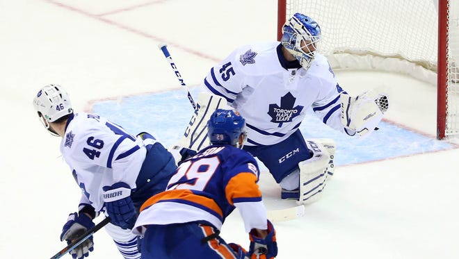 Toronto Maple Leafs goalie Jonathan Bernier (45) makes a glove save on a shot by New York Islanders center Brock Nelson (29) during the third period at Nassau Veterans Memorial Coliseum.