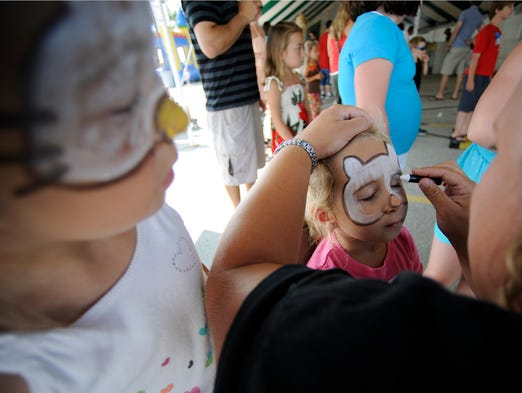 Jamie Lambrecht of Francis Creek, right, decorates the face of Brooklyn Abbet, 4, as her sister, Jersey Larsen, 6, both of Manitowoc, watches. Hundreds came out for fun at the 24th annual Shipbuilders Credit Union Presents Lakeshore Weekend event on Saturday, Aug. 1, 2014 along the lakefront in Manitowoc.  Some of the highlights of the event include dragon boat races, free concerts, a dunk tank, children's games, a 5k Color Fun Run/Walk, and an aqua ball. The event continues on Sunday, Aug. 3 and benefits the Children's Hospital of Wisconsin. Matthew Apgar/HTR Media