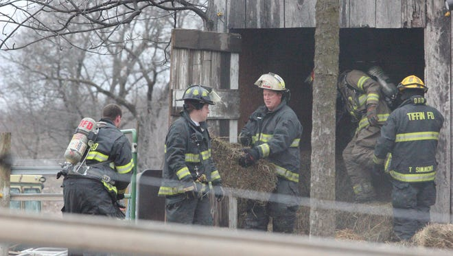 Firefighters carry smoldering hay from a barn, after the building at 3342 Portwood Drive, Homestead, caught fire at about 5:15 p.m. Sunday, March 27.