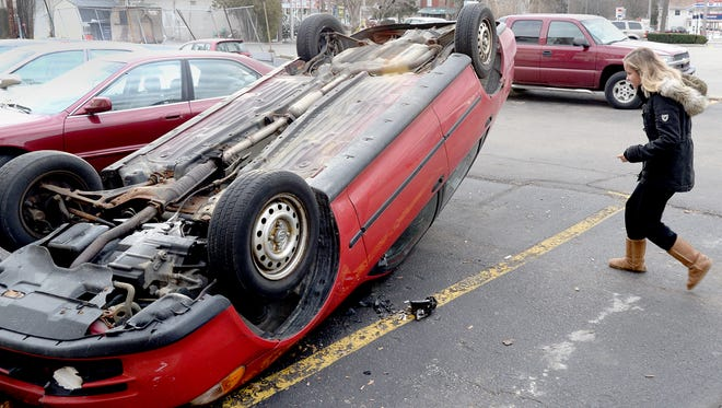 Michigan State University sophomore Caitlyn Kuskowski, looks at an overturned car in the parking lot of her building Sunday, Dec. 8, 2013. Revelers started fires and caused other damage after Saturday's MSU football win over Ohio State.