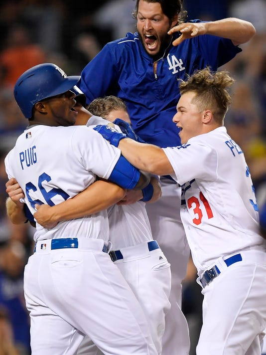 Los Angeles Dodgers' Yasiel Puig, left, Joc Pederson, right, Clayton Kershaw, second from right, and Chase Utley, center, congratulate Corey Seager, second from left, after Seager scored the game-winning run on a double by Adrian Gonzalez during the ninth inning of a baseball game against the San Francisco Giants, Monday, Sept. 19, 2016, in Los Angeles. (AP Photo/Mark J. Terrill)