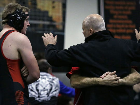 A Pewaukee wrestler gets instruction from his coaches as the 20th Cheesehead Invitational in early January at Kaukauna High School.