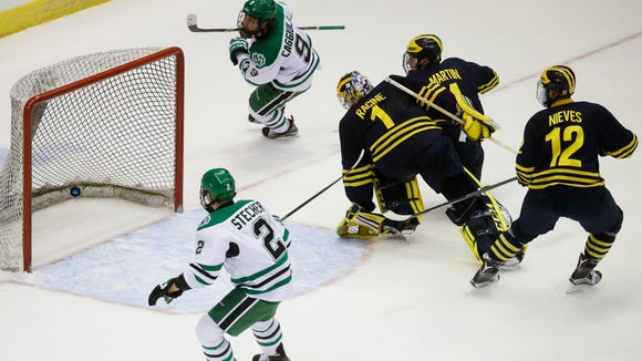 North Dakota's Drake Caggiula (9) scores on Michigan goalie Steve Racine (1) as Michigan's Cutler Martin, second from right, and Cristoval Nieves (12) and North Dakota's Troy Stecher (2) watch during the first period of the Midwest Regional final of the men's NCAA college hockey tournament, Saturday, March 26, 2016, in Cincinnati.