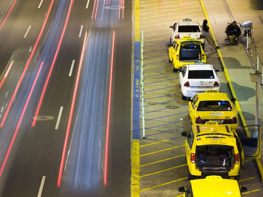 Taxis wait to pick up passengers at Phoenix Sky Harbor International Airport on Friday, Dec. 16, 2015.