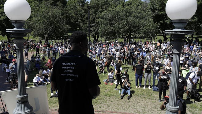 """Benjamin Watson, a former New England Patriots football player, front, addresses an audience in Boston during an event called """"Boston Pray: Seeking Unity and Justice,"""" held to call for an end to racial injustice, triggered by the death of George Floyd, an African American man who died on May 25 as a Minneapolis police officer pressed his knee into his neck."""