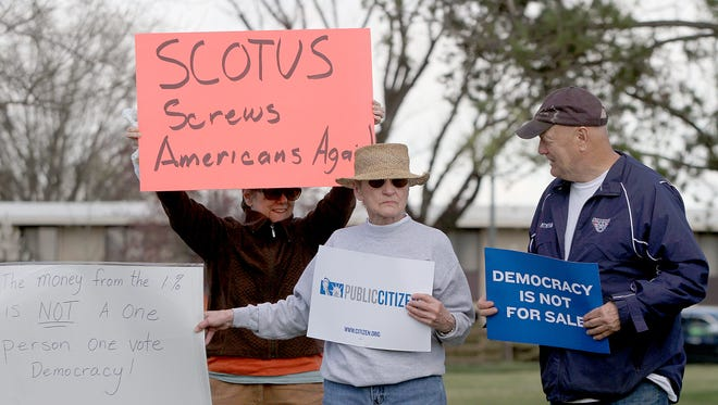 Members of Move to Amend Tri-Cities  at John Dam Plaza in Richland, WA protest the Supreme Court ruling in McCutcheon v. FEC that lifted limits on individual contributions in the two-year campaign cycle.