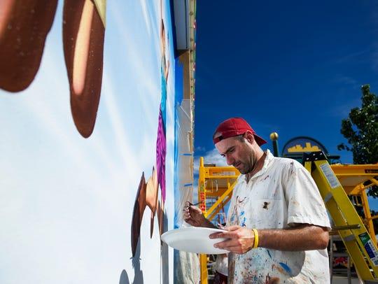 Rafael Blanco works on his mural art outside of Circus