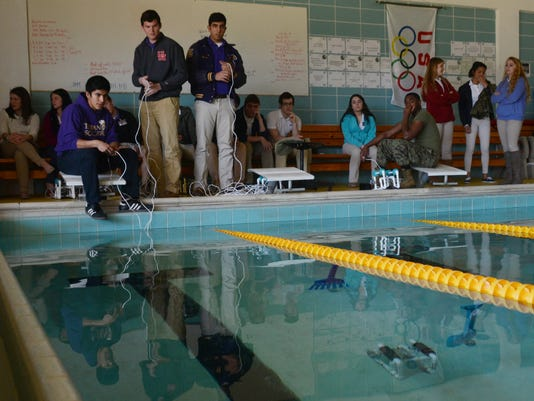 ANI Underwater Robots Alexandria Senior High students Jonathan Turrubiartes (far left), Zachary Price and Ahmad Salam are in Julia James' physics class and have built underwater robots. Turrubiartes and Price operate their robot with a remote control to ha
