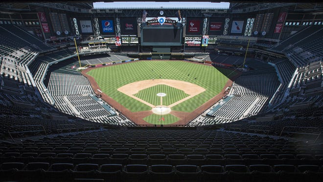 Chase Field grounds crew mow the great expanse of turf.
