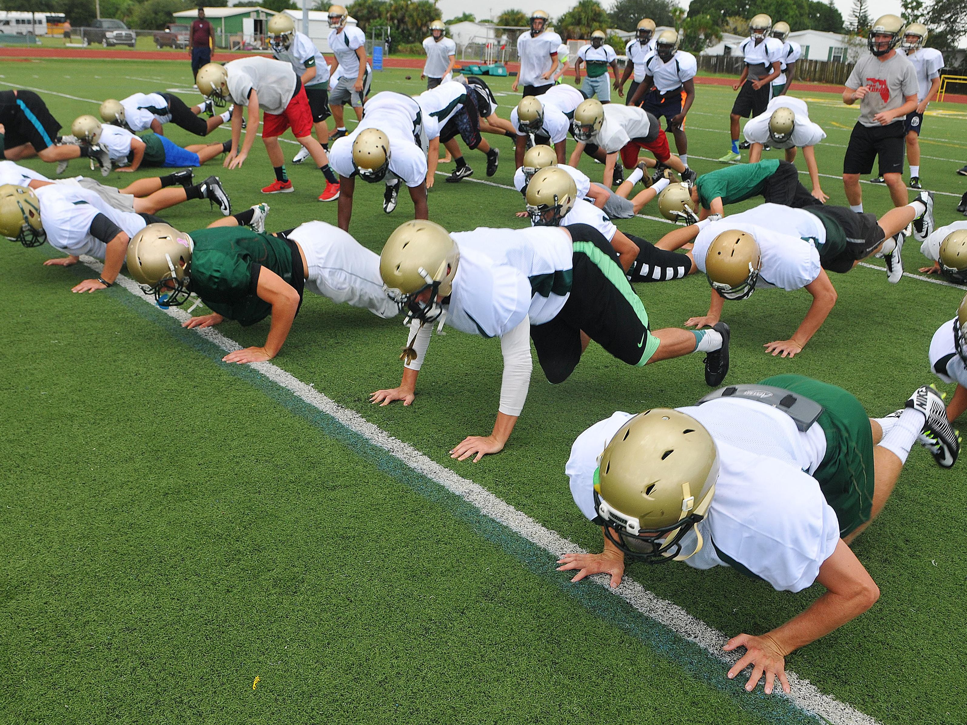 Melbourne Central Catholic Football players warm up for Thursday football practice.