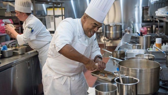 Chef Shawn Loving prepares a fish dish. His apprentice, Christina Nestorovski, assists Chef Loving.