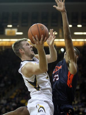 Iowa's Josh Oglesby draws a foul from Pepperdine's A.J. John during Monday's 73-62 Hawkeye win.